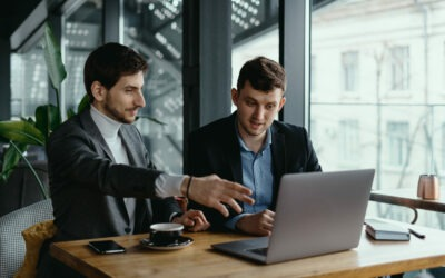 Two businessmen pointing laptop screen while discussing